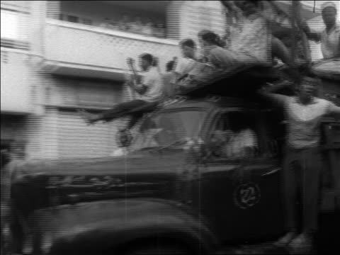 b/w 1960s pan demonstrators piled onto truck during revolution / dominican republic / newsreel - イスパニョーラ点の映像素材/bロール