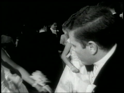 B/W 1960s dolly shot out of couples in formalwear doing the Twist at dance