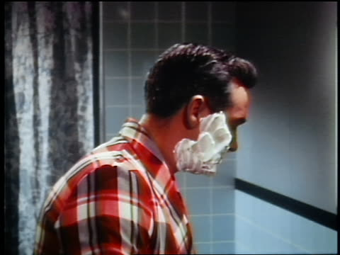 1960s dolly shot to close up profile man putting shaving cream on face + starting to shave with razor - handsome people stock videos & royalty-free footage