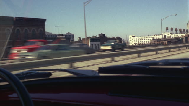 1960s ws pov driving on expressway through industrial district - anno 1968 video stock e b–roll