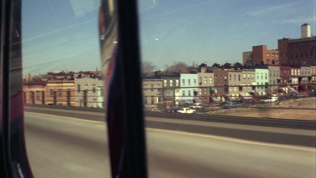 1960s WS POV Driving on expressway through residential district