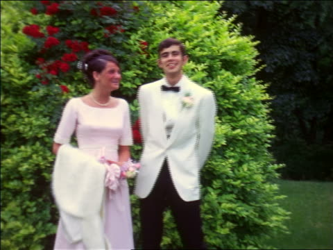 vidéos et rushes de 1960s embarrassed teen couple in formalwear posing by bush + laughing / home movie - couple d'adolescents