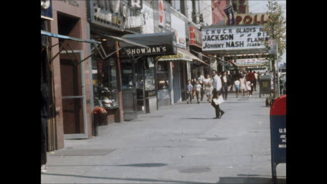 1960s establishing shot of people walking along 125th street near the apollo theater in harlem. - new york city stock videos & royalty-free footage