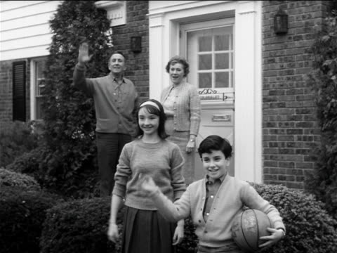 b/w 1960s family standing in front yard waving / children run off parents enter house / industrial - 1960 stock videos & royalty-free footage