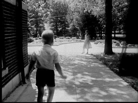 '1960s FILM MONTAGE WS Boy running up sidewalk and away from school and nun/ MS Boy jumping into mother's arms/ St. Louis, Missouri'