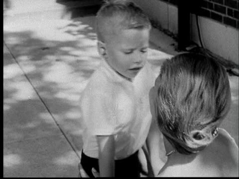 """1960s FILM MONTAGE MS Deaf boy with hearing aid struggling to say """"I love you"""" to his mother/ WS Mother hugging boy/ St. Louis"""