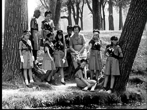 """1960s film montage ws girl scouts leaning in park on edge of water/ ms girl throwing bread crumbs into water/ st. louis, missouri"" - boy scout stock videos and b-roll footage"