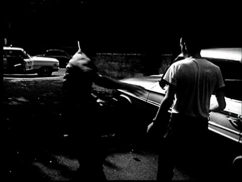 """1960s FILM MONTAGE MS Police arriving to catch young man stealing hubcap in alley/ MS Police frisking man up against car/ CU Man's hands on car/ St. Louis, Missouri"""