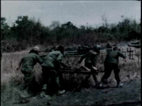 1960s TS First Infantry Division soldiers evacuating casualty to helicopter / Vietnam