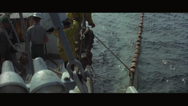 1960s ws ha fishermen on boat pulling net - fishing boat stock videos & royalty-free footage
