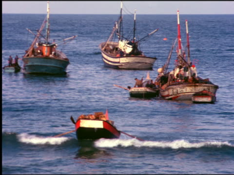 1960s fishing boats anchored in ocean near shore / rowboat in foreground / Portugal