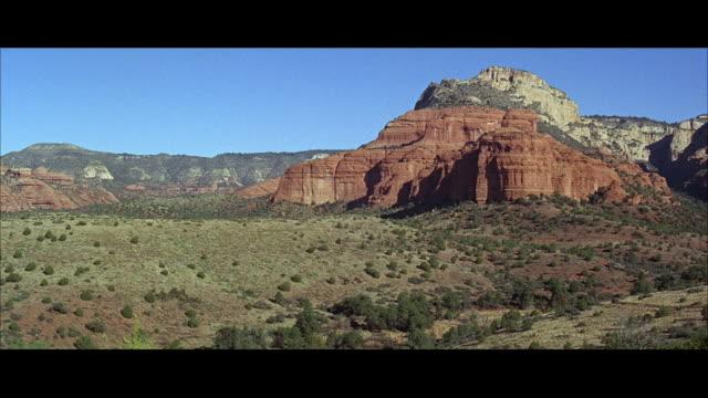 vídeos de stock e filmes b-roll de 1960s ls ws pan five men riding up slope, craggy mountains in background - grupo pequeno de animais