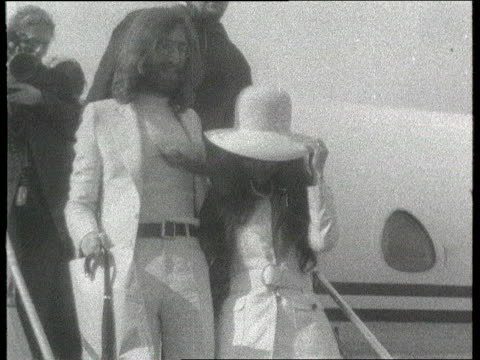 W 1960s Footage John Lennon and wife Yoko Ono towards down steps from aeroplane MSs Lennon and Ono along PAN CF = B0555537 or B0558461 203041 to...