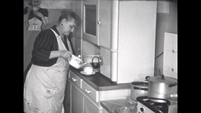 1960s former gdr honest couple housewife preparing coffee in the kitchen brings it to her husband in the living room they`re drinking it he reads a... - hausfrau stock-videos und b-roll-filmmaterial
