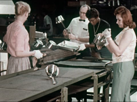 1960s four workers shining and inspecting kitchenware on conveyor belt