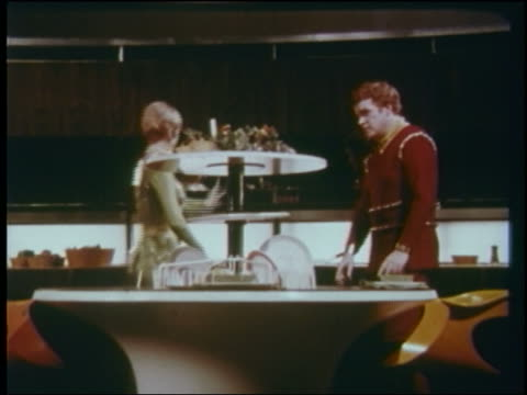 1960s futuristic couple watches as dishwasher lowers into table / lights go on in glass refrigerator - 1960 stock videos and b-roll footage