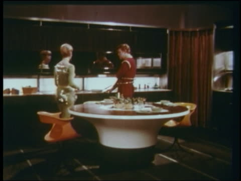1960s futuristic couple watches as dishwasher rises up out of center of table in kitchen - lavastoviglie video stock e b–roll