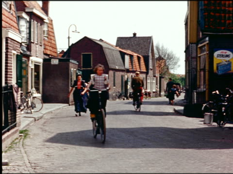 1960s girl riding bicycle + people walking on village street / netherlands - 1960 stock videos and b-roll footage