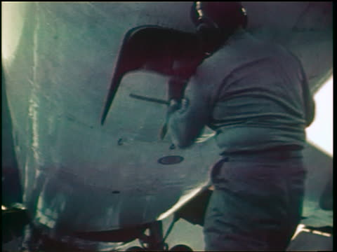 1960s ground crew member closing hatch on belly of military airplane during emergency / documentary