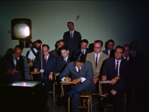 1960s group of businessmen sitting at desks taking notes during seminar / overhead projector in foreground - overhead projector stock videos & royalty-free footage