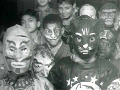 B/W 1960s group of children in Halloween costumes looking at camera / some in masks / home movie