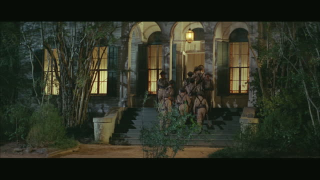 1960s ws group of viet cong guards entering house in woods - ベトコン点の映像素材/bロール
