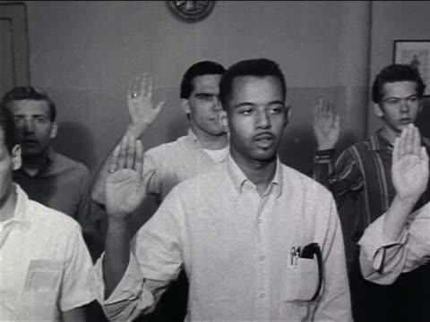 B/W 1960s PAN group of young men holding up hands saying Oath of Enlistment / Vietnam War