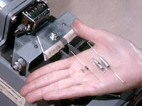 CU 1960s Hand holding resistors over lead bending machine, California, USA