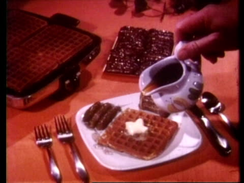 1960s hand pouring syrup onto waffles on plate with sausages - waffles stock videos and b-roll footage