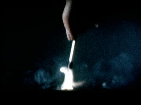 slo mo cu 1960s hand striking match - streichholz stock-videos und b-roll-filmmaterial