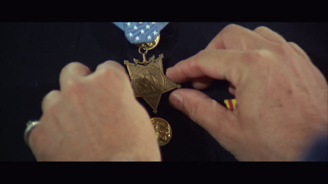 vidéos et rushes de 1960s cu zi hands pinning medal on soldier's uniform - médaille récompense