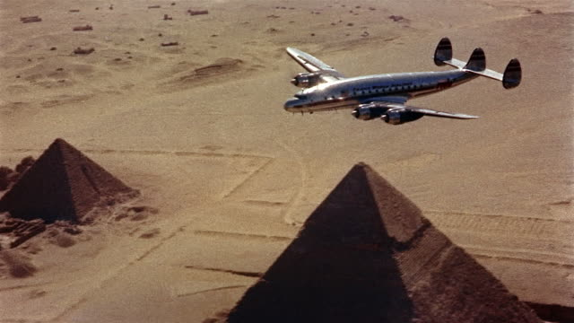 vidéos et rushes de 1960s high angle airplane flying above the pyramids / cairo - égypte