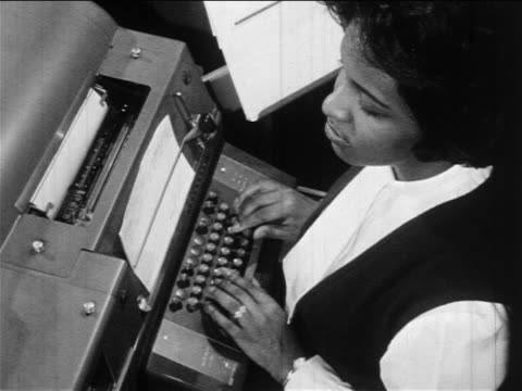 b/w 1960s high angle black woman typing on typewriter / documentary - sekretärin stock-videos und b-roll-filmmaterial