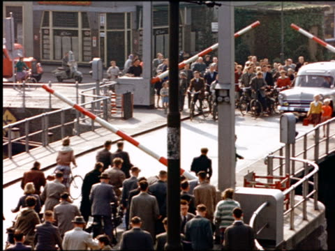 vídeos de stock, filmes e b-roll de 1960s high angle car, people walking + people riding bicycles across drawbridge when barriers rise / holland - drawbridge
