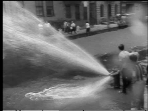 vídeos y material grabado en eventos de stock de b/w 1960s high angle pan children playing under fire hydrant spray on city street - boca de riego