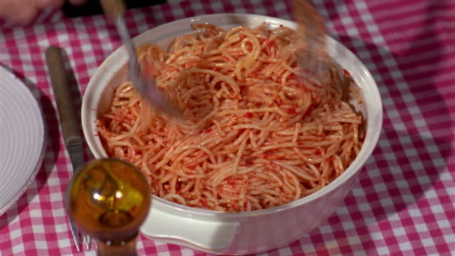 1960s high angle close up mixing pasta and placing on plate