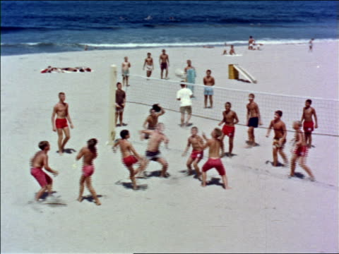1960s high angle long shot boys in swimsuits playing volleyball on beach / los angeles / educational - 1960 stock-videos und b-roll-filmmaterial