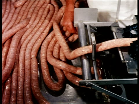 1960s high angle PAN man's hands feeding sausage into machine breaking it into links + tying it