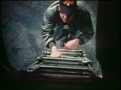 1960s high angle pilot climbing ladder into airplane during emergency / Cold War / documentary