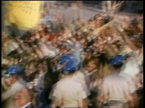 stockvideo's en b-roll-footage met 1960s high angle pan policemen in helmets blocking crowd of protesters giving peace sign at demonstration - vredesteken handgebaar