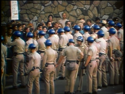 1960s high angle rows of policemen in helmets blocking crowd of protesters at peace demonstration - friedensdemonstration stock-videos und b-roll-filmmaterial
