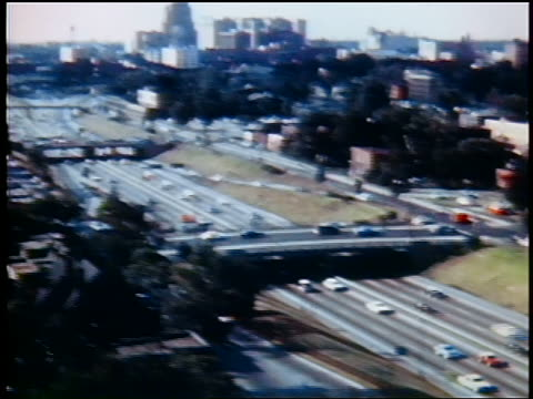 stockvideo's en b-roll-footage met 1960s high angle wide shot tilt down pan traffic on highway with detroit skyline in background / industrial - pan american highway