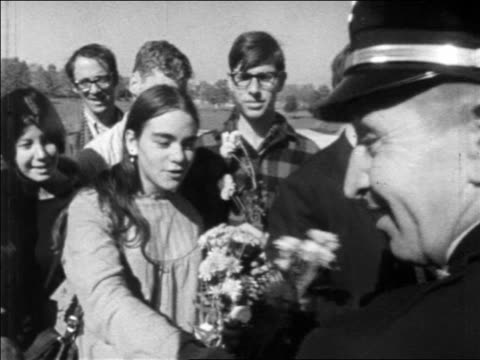 b/w 1960s hippie girl in group giving flowers to soldier outdoors / demonstration / newsreel - hippy video stock e b–roll