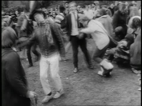vídeos de stock, filmes e b-roll de b/w 1960s hippies dancing in park / woman riding on man's shoulders / seattle / newsreel - hippie