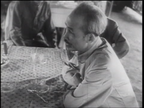 b/w 1960s ho chi minh sitting at table talking gesturing outdoors / north vietnam / documentary - north vietnam stock videos and b-roll footage