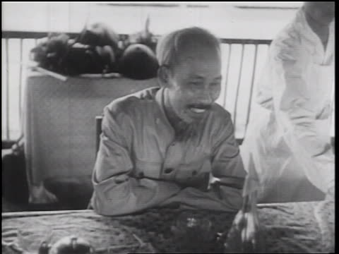 b/w 1960s ho chi minh smiling nodding head sitting at table on patio / north vietnam - editorial bildbanksvideor och videomaterial från bakom kulisserna