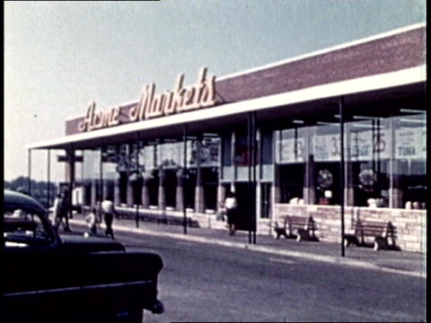 1960s Home Markets supermarket exterior with car parked in front / USA