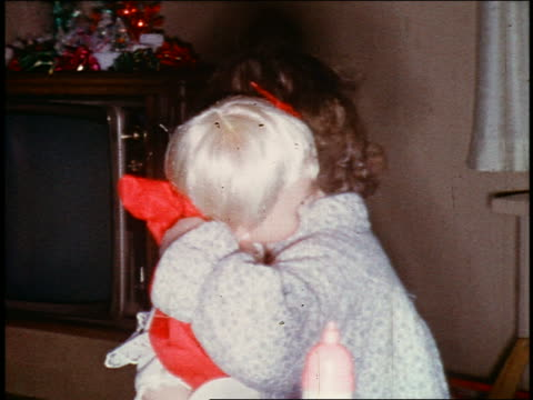 1960s home movie close up small girl in pajamas hugging + kissing doll on christmas morning - only girls stock videos and b-roll footage