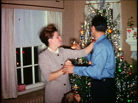 vídeos de stock, filmes e b-roll de 1960s home movie couple kissing, toasting + posing in front of christmas tree in living room - decoração de natal