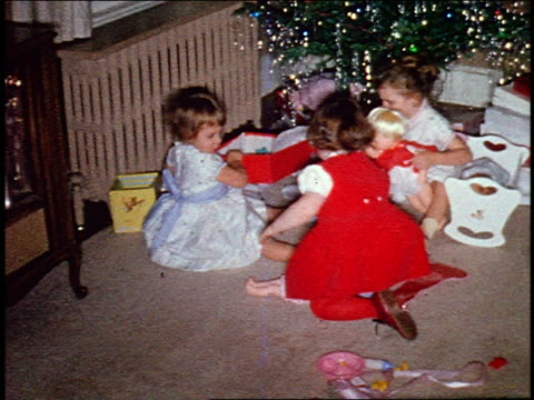 1960s home movie high angle three small girls opening gift + playing with dolls near christmas tree - doll stock videos and b-roll footage